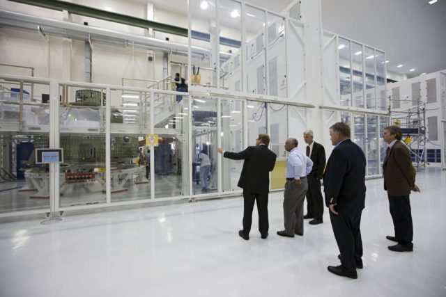 CAPE CANAVERAL, Fla. – Charles Bolden, NASA administrator, center, is shown the Orion capsule that will make an uncrewed flight test in 2014.  The spacecraft is in the high bay at the Operations and Checkout Building at NASA's Kennedy Space Center in Florida. Photo credit: NASA/Kim Shifflett KSC-2012-4245