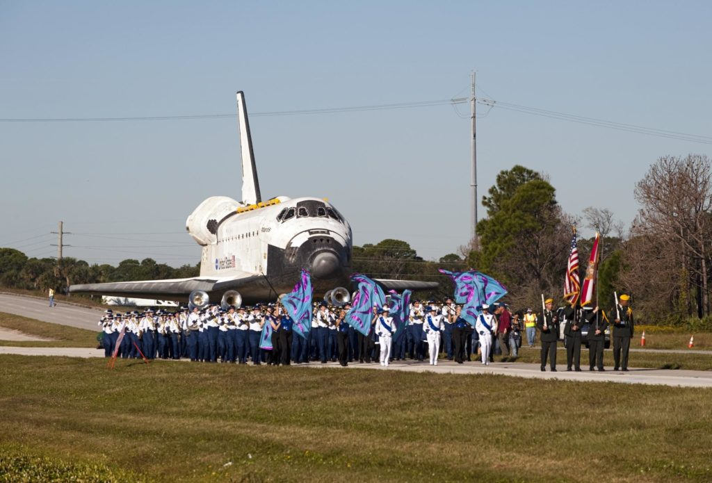 CAPE CANAVERAL, Fla. – Led by the Merritt Island High School color guard and the Titusville High School band, the space shuttle Atlantis is transported along NASA Causeway at NASA's Kennedy Space Center in Florida on its 10-mile journey to the Kennedy Space Center Visitor Complex where it will be put on public display.      As part of transition and retirement of the Space Shuttle Program, Atlantis is to be displayed at Kennedy's Visitor Complex beginning in the summer of 2013. Over the course of its 26-year career, Atlantis traveled 125,935,769 miles during 307 days in space over 33 missions. For more information, visit http://www.nasa.gov/transition Photo credit: NASA/ Tony Gray KSC-2012-6039