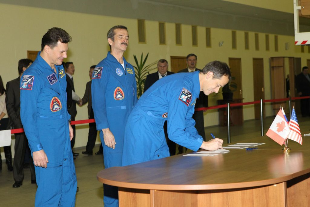 At the Gagarin Cosmonaut Training Center in Star City, Russia, Expedition 34/35 NASA Flight Engineer Tom Marshburn signs in for the start of two days of certification exams for flight Nov. 27, 2012 as his crewmates, Soyuz Commander Roman Romanenko (left) and Flight Engineer Chris Hadfield of the Canadian Space Agency (right) look on. Marshburn, Romanenko and Hadfield and their backups are in the final weeks of training for launch on the Soyuz TMA-07M spacecraft from the Baikonur Cosmodrome in Kazakhstan on Dec. 19 for 5 ½ months on the International Space Station. NASA/Stephanie Stoll jsc2012e238542