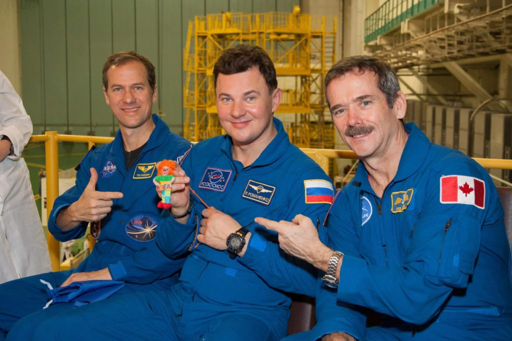 "At the Baikonur Cosmodrome in Kazakhstan, Expedition 34/35 Soyuz Commander Roman Romanenko (center) holds a toy ""talisman"" that his 9-year old daughter, Anastasia, gave him to hang over his seat in the Soyuz TMA-07M spacecraft as a zero-G indicator during launch with his crewmates, Flight Engineer Tom Marshburn of NASA (left) and Flight Engineer Chris Hadfield of the Canadian Space Agency (right). The toy, named ""Klyopa"" for the Egyptian queen Cleopatra, was unveiled during a ""fit check"" dress rehearsal Dec. 7, 2012 in Baikonur leading to the crew's launch Dec. 19 for a five-month mission on the International Space Station. Photo Credit: NASA/Victor Zelentsov jsc2012e241481"