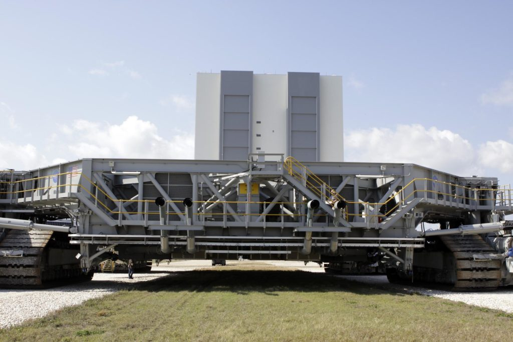CAPE CANAVERAL, Fla. – At NASA's Kennedy Space Center in Florida, the crawler-transporter 2, or CT-2, is on its way from the Vehicle Assembly Building to the Park Site west of the building. The transporter has new brakes and mufflers and a recently-painted white roof deck.    The Ground Systems Development and Operations Program office at Kennedy is overseeing the upgrades to CT-2 so that it can carry NASA's Space Launch System heavy-lift rocket, which is under design, and new Orion spacecraft to the launch pad. The crawler-transporters were used to carry the mobile launcher platform and space shuttle to Launch Complex 39 for space shuttle launches for 30 years.  Photo credit: NASA/Jim Grossmann KSC-2013-1506