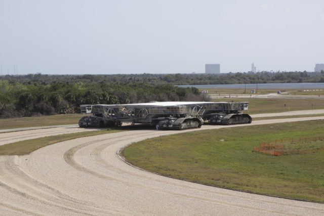 CAPE CANAVERAL, Fla. – At NASA's Kennedy Space Center in Florida, the crawler-transporter 2, or CT-2, is on its way from the Vehicle Assembly Building to the Park Site west of the building. The transporter has new brakes and mufflers and a recently-painted white roof deck.    The Ground Systems Development and Operations Program office at Kennedy is overseeing the upgrades to CT-2 so that it can carry NASA's Space Launch System heavy-lift rocket, which is under design, and new Orion spacecraft to the launch pad. The crawler-transporters were used to carry the mobile launcher platform and space shuttle to Launch Complex 39 for space shuttle launches for 30 years.  Photo credit: NASA/Jim Grossmann KSC-2013-1507