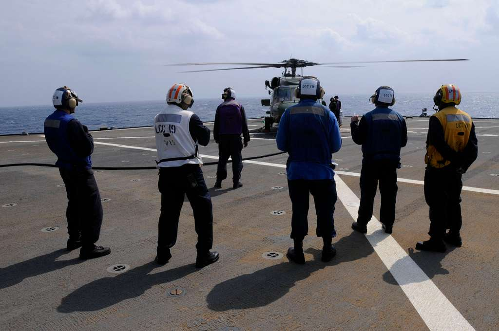 U.S. sailors stand by during the refueling of an SH-60F