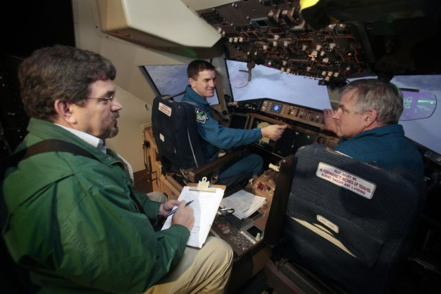 (left to right) NASA Langley aerospace engineer Bruce Jackson briefs astronauts Rex Walheim and Gregory Johnson about the Synthetic Vision (SV) and Enhanced Vision (EV) systems in a flight simulator at the center's Cockpit Motion Facility. The astronauts were training to land the Dream Chaser spacecraft May 15th 2013. credit NASA/David C. Bowman 2013-2363
