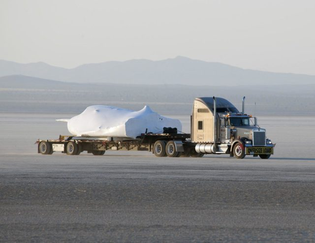EDWARDS, Calif. – ED13-0142-01: With its wings and tail structure removed and shrouded in plastic wrap for ground transport, Sierra Nevada Corporation, or SNC, Space Systems' Dream Chaser engineering test article is hauled across the bed of Rogers Dry Lake at Edwards Air Force Base, Calif., to NASA's Dryden Flight Research Center. The Dream Chaser will begin its approach-and-landing flight test program in collaboration with NASA's Commercial Crew Program this summer.       SNC is one of three companies working with NASA's Commercial Crew Program, or CCP, during the agency's Commercial Crew Integrated Capability, or CCiCap, initiative, which is intended to lead to the availability of commercial human spaceflight services for government and commercial customers. To learn more about CCP and its industry partners, visit www.nasa.gov/commercialcrew. Image credit: NASA/Tom Tschida KSC-2013-2357