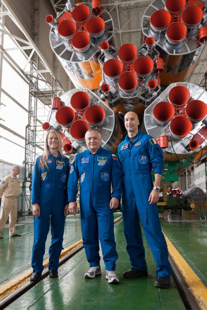 """At the Baikonur Cosmodrome in Kazakhstan, Expedition 36/37 Flight Engineer Karen Nyberg of NASA (left), Soyuz Commander Fyodor Yurchikhin (center) and Flight Engineer Luca Parmitano of the European Space Agency (right) pose for pictures May 24 in front of the first stage engines of their Soyuz rocket in the Integration Facility following the final """"fit check"""" dress rehearsal by the prime and backup crews. Nyberg, Yurchikhin and Parmitano  are preparing for launch May 29, Kazakh time, in the Soyuz TMA-09M spacecraft to begin a 5 ½ month mission on the International Space Station.  NASA/Victor Zelentsov jsc2013e048420"""