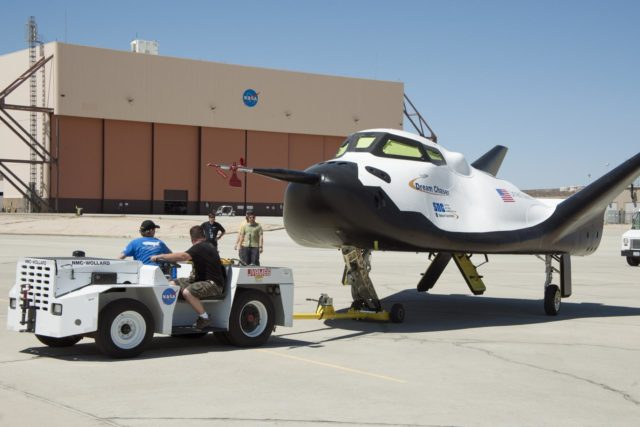 Edwards, Calif. – ED13-164-33 - Sierra Nevada Corporation SNC Space Systems' team members tow the Dream Chaser flight vehicle out to a concrete runway at NASA's Dryden Flight Research Center in California for range and taxi tow tests. The ground testing will validate the performance of the spacecraft's nose skid, brakes, tires and other systems prior to captive-carry and free-flight tests scheduled for later this year.    SNC is one of three companies working with NASA's Commercial Crew Program, or CCP, during the agency's Commercial Crew Integrated Capability, or CCiCap, initiative, which is intended to lead to the availability of commercial human spaceflight services for government and commercial customers. To learn more about CCP and its industry partners, visit www.nasa.gov/commercialcrew. Image credit: NASA/Ken Ulbrich KSC-2013-3020