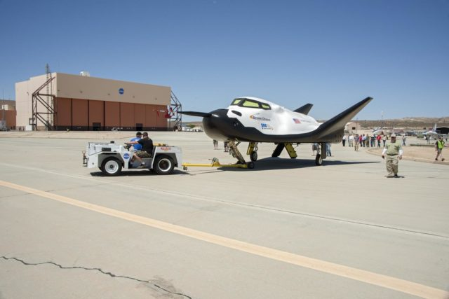 Edwards, Calif. – ED13-164-34 - Sierra Nevada Corporation SNC Space Systems' team members tow the Dream Chaser flight vehicle out to a concrete runway at NASA's Dryden Flight Research Center in California for range and taxi tow tests. The ground testing will validate the performance of the spacecraft's nose skid, brakes, tires and other systems prior to captive-carry and free-flight tests scheduled for later this year.        SNC is one of three companies working with NASA's Commercial Crew Program, or CCP, during the agency's Commercial Crew Integrated Capability, or CCiCap, initiative, which is intended to lead to the availability of commercial human spaceflight services for government and commercial customers. To learn more about CCP and its industry partners, visit www.nasa.gov/commercialcrew. Image credit: NASA/Ken Ulbrich KSC-2013-3021