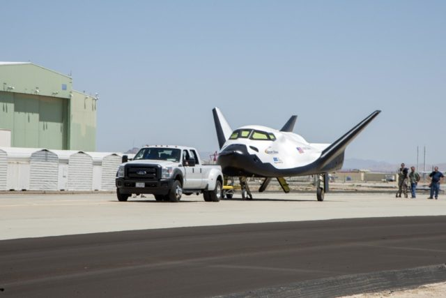 Edwards, Calif. – ED13-164-34 - Sierra Nevada Corporation SNC Space Systems' team members tow the Dream Chaser flight vehicle out to a concrete runway at NASA's Dryden Flight Research Center in California for range and taxi tow tests. The ground testing will validate the performance of the spacecraft's nose skid, brakes, tires and other systems prior to captive-carry and free-flight tests scheduled for later this year.        SNC is one of three companies working with NASA's Commercial Crew Program, or CCP, during the agency's Commercial Crew Integrated Capability, or CCiCap, initiative, which is intended to lead to the availability of commercial human spaceflight services for government and commercial customers. To learn more about CCP and its industry partners, visit www.nasa.gov/commercialcrew. Image credit: NASA/Ken Ulbrich KSC-2013-3022