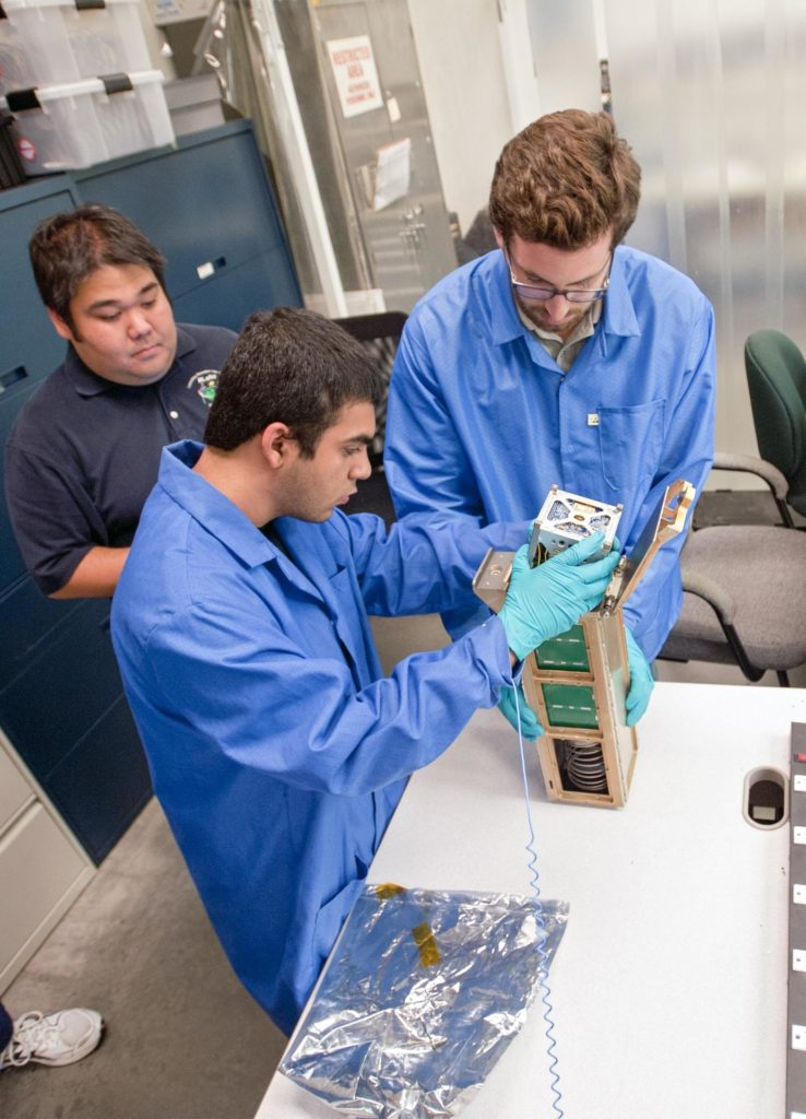 SAN LUIS OBISPO, Calif. – Roland Coelho, third from left, CalPoly program lead, and members of the student launch team load a payload into a Poly Picosatellite Orbital Dispensor, or P-Pod nanolauncher/carrier in the CubeSat lab facility at California Polytechnic Institute, or CalPoly. The payload, which includes sensors and equipment carefully packaged into 4-inch cube sections, will ride in the body of a Garvey Spacecraft Corporation's Prospector P-18D rocket during a June 15 launch on a high-altitude, suborbital flight. Known as a CubeSat, the satellite will record shock, vibrations and heat inside the rocket. It will not be released during the test flight, but the results will be used to prove or strengthen their designs before they are carried into orbit in 2014 on a much larger rocket. Also, a new launcher/carrier of a lightweight design also is being tested for use on future missions to deploy the small spacecraft. The flight also is being watched closely as a model for trying out new or off-the-shelf technologies quickly before putting them in the pipeline for use on NASA's largest launchers. Built by several different organizations, including a university, a NASA field center and a high school, the spacecraft are four-inch cubes designed to fly on their own eventually, but will remain firmly attached to the rocket during the upcoming mission. For more information, visit http://www.nasa.gov/mission_pages/smallsats/elana/cubesatlaunchpreview.html Photo credit: VAFB/Kathi Peoples KSC-2013-2723
