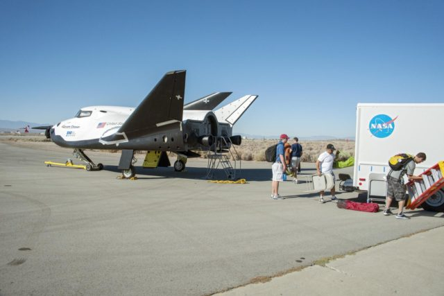 Edwards, Calif. – ED13-0215-016 - Sierra Nevada Corporation SNC Space Systems' team members prepare to tow the Dream Chaser flight vehicle along a concrete runway at NASA's Dryden Flight Research Center in California for range and taxi tow tests. The ground testing will validate the performance of the spacecraft's nose skid, brakes, tires and other systems prior to captive-carry and free-flight tests scheduled for later this year.      SNC is one of three companies working with NASA's Commercial Crew Program, or CCP, during the agency's Commercial Crew Integrated Capability, or CCiCap, initiative, which is intended to lead to the availability of commercial human spaceflight services for government and commercial customers. To learn more about CCP and its industry partners, visit www.nasa.gov/commercialcrew. Image credit: NASA/Ken Ulbrich KSC-2013-3023