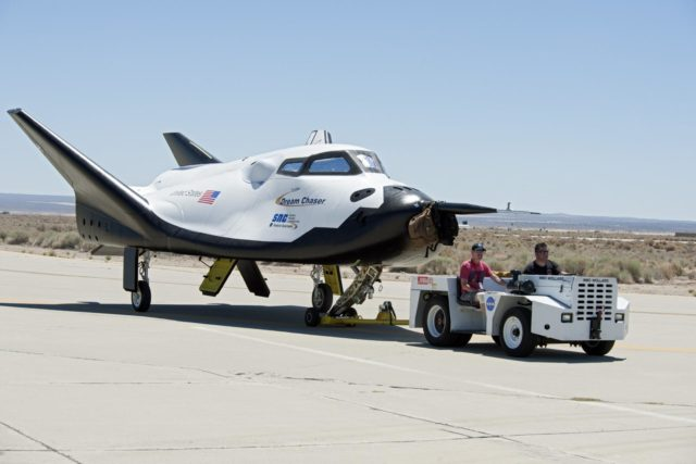 Edwards, Calif. – ED13-0215-072 - Sierra Nevada Corporation SNC Space Systems' team members tow the Dream Chaser flight vehicle along a concrete runway at NASA's Dryden Flight Research Center in California for range and taxi tow tests. The ground testing will validate the performance of the spacecraft's nose skid, brakes, tires and other systems prior to captive-carry and free-flight tests scheduled for later this year.  SNC is one of three companies working with NASA's Commercial Crew Program, or CCP, during the agency's Commercial Crew Integrated Capability, or CCiCap, initiative, which is intended to lead to the availability of commercial human spaceflight services for government and commercial customers. To learn more about CCP and its industry partners, visit www.nasa.gov/commercialcrew. Image credit: NASA/Ken Ulbrich KSC-2013-3025