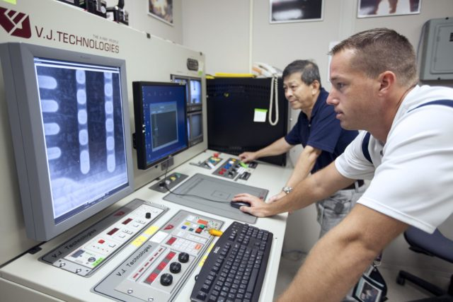 CAPE CANAVERAL, Fla. – In Hangar N at Cape Canaveral Air Force Station, PaR Systems, Inc. development engineer Wayne Cheng, left, and operations engineer Jeff Elston operate the controller for a robotic system used in nondestructive testing. The 11-axis robotic system takes X-ray images of hardware for evaluation.      NASA's Kennedy Space Center in Florida recently established a partnership agreement with PaR Systems, Inc. of Shoreview, Minn., for operation of the Hangar N facility and its nondestructive testing and evaluation equipment. As the spaceport transitions from a historically government-only launch facility to a multi-user spaceport for both federal and commercial customers, partnerships between the space agency and other organizations will be a key element in that effort. Hangar N is located at Cape Canaveral Air Force Station adjacent to Kennedy and houses a unique inventory of test and evaluation equipment and the capability for current and future mission spaceflight support. Photo credit: NASA/ Dimitri Gerondidakis KSC-2013-3221