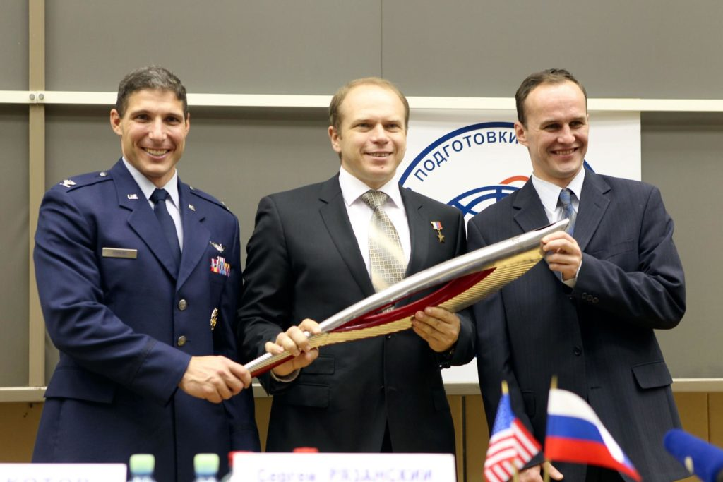 At the Gagarin Cosmonaut Training Center in Star City, Russia, Expedition 37/38 Flight Engineer Michael Hopkins of NASA (left), Soyuz Commander Oleg Kotov (center) and Flight Engineer Sergey Ryazanskiy (right) hold a replica of the Olympic torch Sept. 6 following a crew news conference at their training facility outside Moscow. The trio is preparing for their launch to the International Space Station from the Baikonur Cosmodrome in Kazakhstan on Sept. 26, Kazakh time, aboard the Soyuz TMA-10M spacecraft. The torch that will light the Olympic flame at the Opening Ceremonies of the Winter Olympics in Sochi, Russia Feb. 7, 2014 will be flown the space station by another crew in November and brought home several days later as part of a global and galactic Olympic relay.  NASA/Stephanie Stoll jsc2013e080227