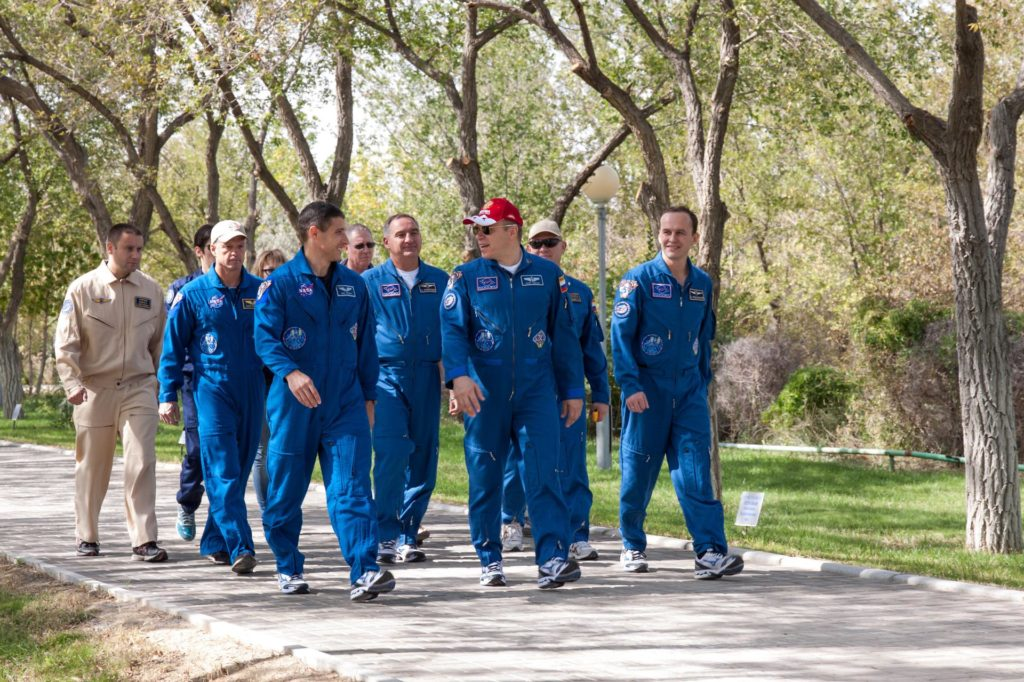 """Expedition 37/38 Flight Engineer Michael Hopkins of NASA (front row, left), Soyuz Commander Oleg Kotov (front row, center) and Flight Engineer Sergey Ryazanskiy (front row, right) lead a procession down the """"Walk of Cosmonauts"""" behind their Cosmonaut Hotel crew quarters in Baikonur, Kazakhstan Sept. 18. Behind the trio are their backups from left to right, Steve Swanson of NASA, Alexander Skvortsov and Oleg Artemyev. Hopkins, Kotov and Ryazanskiy are set to launch Sept. 26, Kazakh time, from the Baikonur Cosmodrome on their Soyuz TMA-10M spacecraft for a five and a half month mission on the International Space Station.  NASA/Victor Zelentsov jsc2013e087987"""