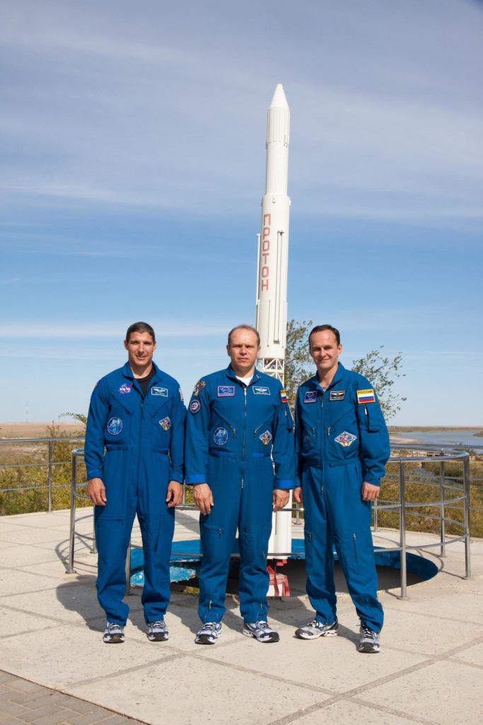 Behind their Cosmonaut Hotel crew quarters in Baikonur, Kazakhstan, Expedition 37/38 Flight Engineer Michael Hopkins of NASA (left) Soyuz Commander Oleg Kotov (center) and Flight Engineer Sergey Ryazanskiy (right) pose for pictures Sept. 18 as they enter the homestretch of their pre-flight training. Hopkins, Kotov and Ryazanskiy are set to launch Sept. 26, Kazakh time, from the Baikonur Cosmodrome on their Soyuz TMA-10M spacecraft for a five and a half month mission on the International Space Station.  NASA/Victor Zelentsov jsc2013e087990