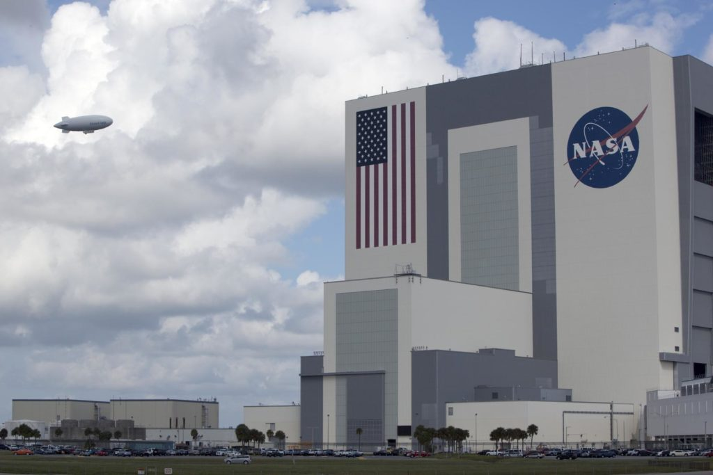 """CAPE CANAVERAL, Fla. -- An airship from the British Broadcasting Corp., or BBC, flies over the processing facilities in Launch Complex 39 toward the Vehicle Assembly Building at NASA's Kennedy Space Center in Florida.    A team of scientists from the BBC's television project """"Cloud Lab"""" are conducting a number of experiments aboard the airship as it flies across the U.S., exploring all aspects of the Earth's atmosphere. One of the experiments is NASA's Microorganisms in the Stratosphere, or MIST, which is designed to measure the microbial survival and cellular responses to exposure in the upper atmosphere. Photo credit: NASA/Dimitri Gerondidakis KSC-2013-3603"""