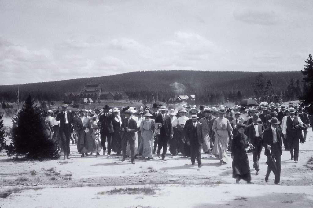 Tourists crossing the runoff channel by Grand Geyser; JP Clum Lantern; Around 1910