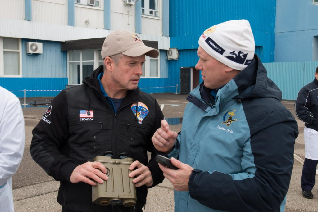 "2014-03-14-16-31-24-2[1] Outside the Integration Facility at the Baikonur Cosmodrome in Kazakhstan, Expedition 39/40 Flight Engineer Steve Swanson of NASA (left) and Flight Engineer Oleg Artemyev of the Russian Federal Space Agency (Roscosmos; right) discuss the use of binoculars and GPS equipment March 14 during a ""fit check"" dress rehearsal that is part of the crew's final training. Swanson, Artemyev and Soyuz Commander Alexander Skvortsov Roscosmos are scheduled to launch to the International Space Station March 26 (Kazakh time) for the start of a six-month mission.  NASA/Victor Zelentsov jsc2014e026286"