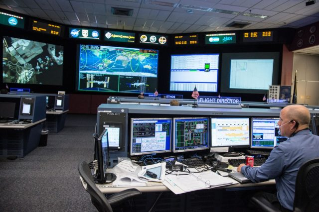 DATE: 3-27-14.LOCATION: Bldg. 30 - FCR-1 (30M/231).SUBJECT: Expedition 39 flight controllers on console with Flight Director Ron Spencer watch the approach of the Soyuz 39 crew docking to the ISS from FCR-1..PHOTOGRAPHER: Lauren Harnett jsc2014e031521