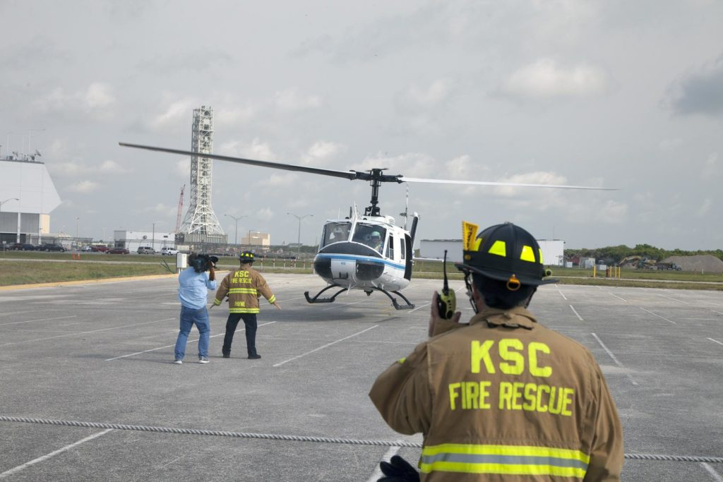 CAPE CANAVERAL, Fla. -- At NASA's Kennedy Space Center in Florida, agency Fire Rescue personnel direct an agency helicopter in for a landing during a training exercise.      The activity taking place in Kennedy's Launch Complex 39 turn-basin parking lot was only one of several drills. It was part of a new training program that was developed by Kennedy's Fire Rescue department along with NASA Aircraft Operations to sharpen the skills needed to help rescue personnel learn how to collaborate with helicopter pilots in taking injured patients to hospitals as quickly as possible. Photo credit: NASA/Dan Casper KSC-2014-2765