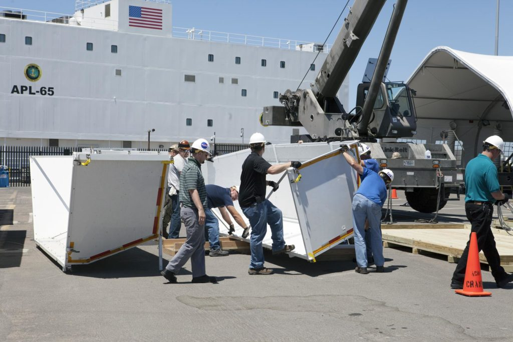 SAN DIEGO, Calif. – Workers prepare to assemble the crew module transportation fixture for the Orion boilerplate test vehicle at the Mole Pier at Naval Base San Diego in California. The test vehicle will be moved from the pier to a warehouse at the naval base. The Ground Systems Development and Operations Program, Lockheed Martin and the U.S. Navy are evaluating the hardware and processes for preparing the Orion crew module for Exploration Flight Test-1, or EFT-1, for overland transport from the naval base to NASA's Kennedy Space Center in Florida.    Orion is the exploration spacecraft designed to carry astronauts to destinations not yet explored by humans, including an asteroid and Mars. It will have emergency abort capability, sustain the crew during space travel and provide safe re-entry from deep space return velocities. The first unpiloted test flight of the Orion is scheduled to launch later this year atop a Delta IV rocket from Cape Canaveral Air Force Station in Florida to an altitude of 3,600 miles above the Earth's surface. The two-orbit, four-hour flight test will help engineers evaluate the systems critical to crew safety including the heat shield, parachute system and launch abort system. For more information, visit http://www.nasa.gov/orion. Photo credit: NASA/Kim Shiflett KSC-2014-2591