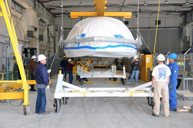 VANDENBERG AIR FORCE BASE, Calif. – Workers lower a half section of the 10-foot-diameter fairing for NASA's Soil Moisture Active Passive mission, or SMAP, onto a hardware dolly in the Building 836 high bay on south Vandenberg Air Force Base in California.    The fairing will protect the SMAP spacecraft from the heat and aerodynamic pressure generated during its ascent to orbit aboard a United Launch Alliance Delta II rocket from Space Launch Complex 2. SMAP will provide global measurements of soil moisture and its freeze/thaw state. These measurements will be used to enhance understanding of processes that link the water, energy and carbon cycles, and to extend the capabilities of weather and climate prediction models. SMAP data will also be used to quantify net carbon flux in boreal landscapes and to develop improved flood prediction and drought monitoring capabilities. Launch is scheduled for November 2014. To learn more about SMAP, visit http://smap.jpl.nasa.gov.  Photo credit: NASA/U.S. Air Force 30th Space Wing KSC-2014-2877