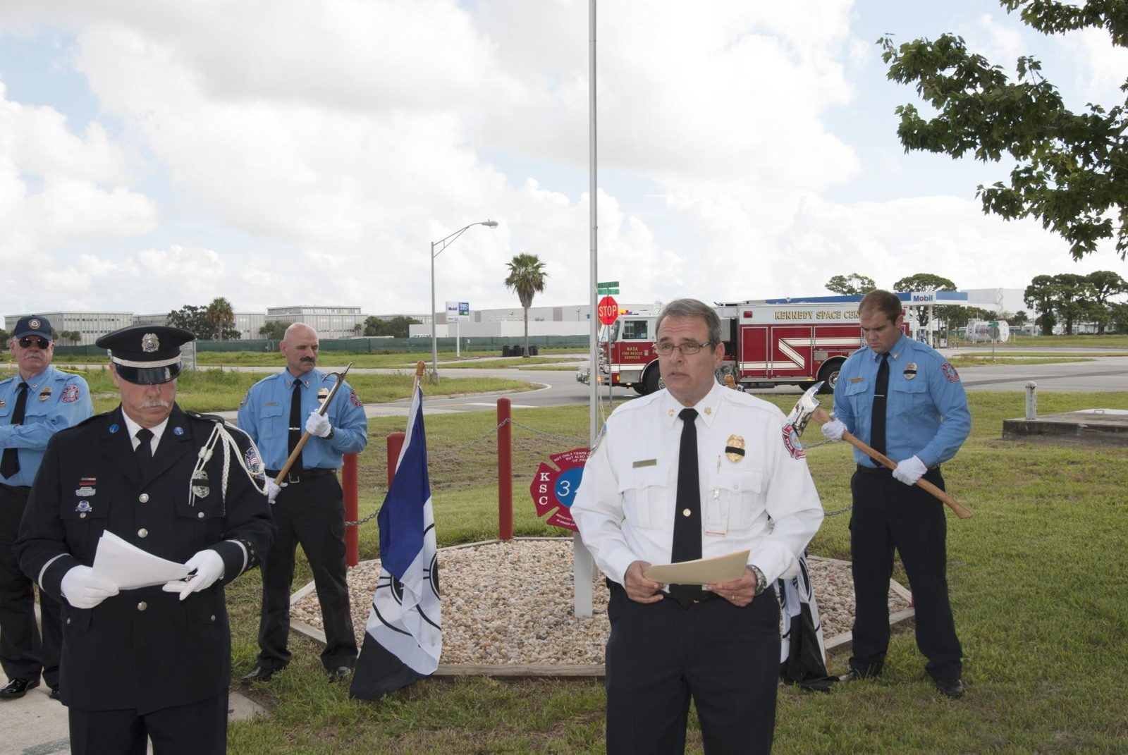 Cape Canaveral, Fla. – At Fire Station 1 at NASA's Kennedy Space Center in Florida, Kennedy Space Center Fire Chief Richard Anderson, center and Commander of the Honor Guard James Dumont, left, share emotional words at the 9/11 memorial during a ceremony held by Kennedy's Fire and Rescue personnel. Behind the pair are members of NASA's Protective Services. Kennedy Fire and Rescue Services commemorated the 13th anniversary of 9/11 with a ceremony that included a minute of silence at 10:28 a.m., which was the moment of collapse of the north tower of the World Trade Center. Photo credit: Jim Grossmann KSC-2014-3802