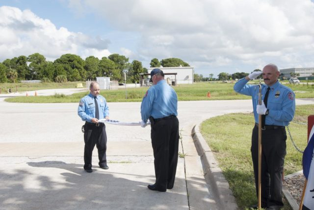 Cape Canaveral, Fla. – At Fire Station 1 at NASA's Kennedy Space Center in Florida, Gabe Wingard and Steve Dudgeon, both with NASA's Protective Services, fold the commemorative flag during a ceremony held by Kennedy's Fire and Rescue personnel. Kennedy Fire and Rescue Services commemorated the 13th anniversary of 9/11 with a ceremony that included a minute of silence at 10:28 a.m., which was the moment of collapse of the north tower of the World Trade Center. Photo credit: Jim Grossmann KSC-2014-3805