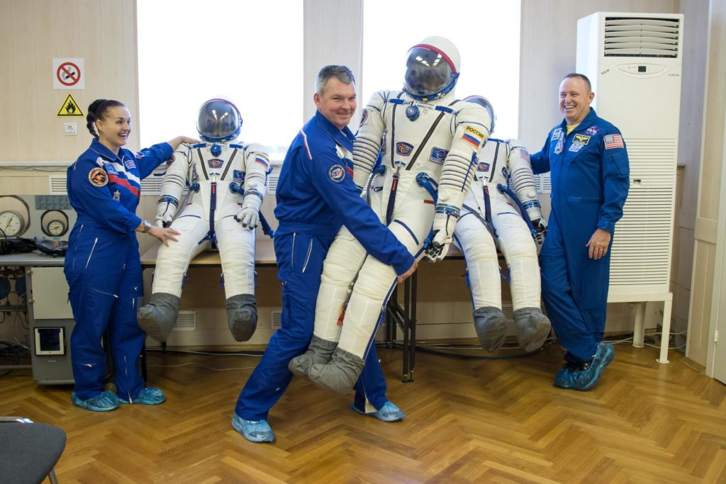 """13-15-42-33-2:     (13 Sept. 2014) --- At the Baikonur Cosmodrome in Kazakhstan, Expedition 41/42 Soyuz Commander Alexander Samokutyaev of the Russian Federal Space Agency (Roscosmos, center) enjoys a light moment with his Russian Sokol launch and entry suit Sept. 13 during the first of two """"fit check"""" dress rehearsal activities. Looking on are his crewmates, Flight Engineer Elena Serova of Roscosmos (left) and Flight Engineer Barry Wilmore of NASA (right). The trio will launch on Sept. 26, Kazakh time, in the Soyuz TMA-14M spacecraft to begin a 5 ½ month mission on the International Space Station. Serova will become the fourth Russian woman to fly in space.  Photo credit: NASA/Victor Zelentsov jsc2014e080531"""