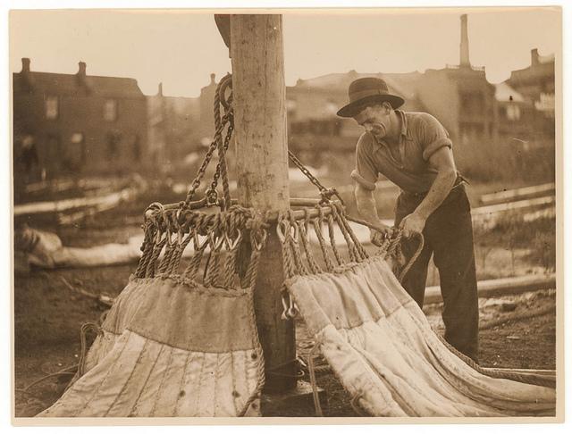 """Circus worker prepares to hoist the """"big top"""", n.d., by Sam Hood"""