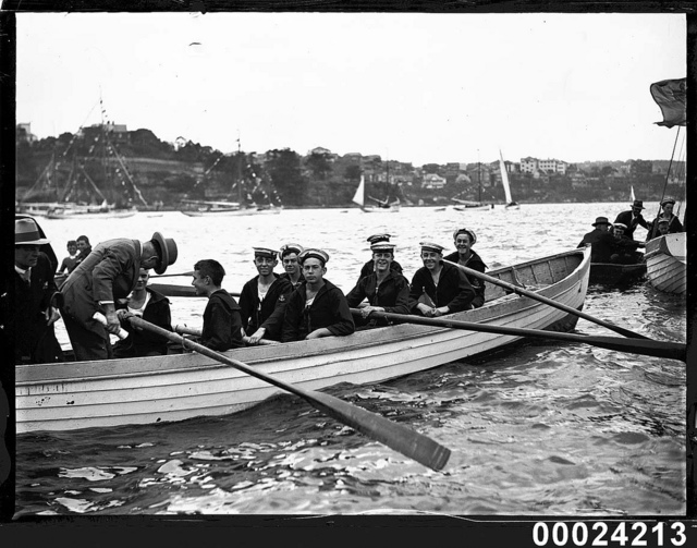 Opening yacht season, merchant sailors and two men wearing suits in a row boat, 1920s