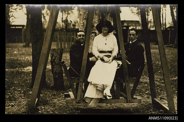 Photographic postcard of a two young men and a woman on a wooden swing