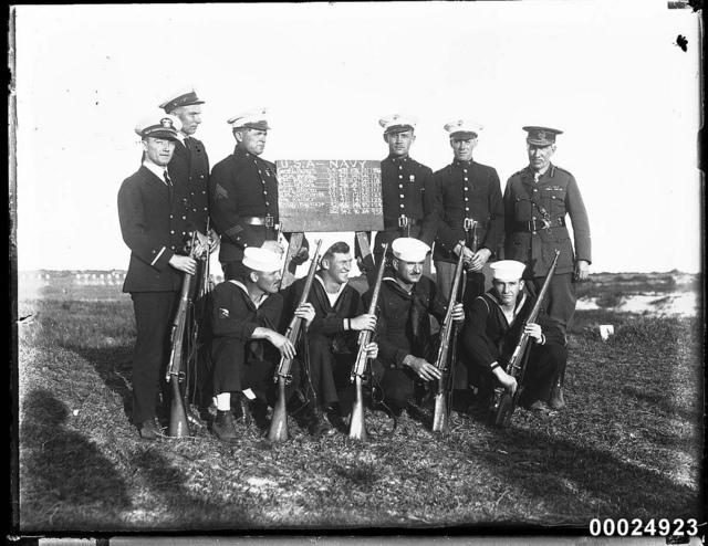 United States officers and sailors with riflemen assembled around a tally board