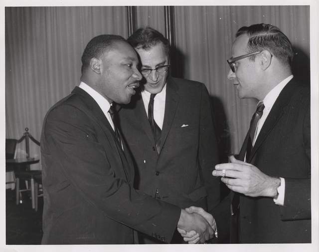 Martin Luther King, Jr. talking with Shad Polier while shaking hands with unidentified smoking man at American Jewish Congress fundraising event