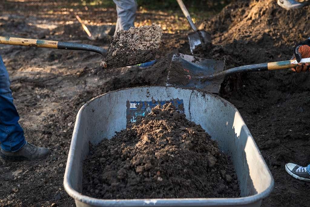 Volunteers shovel dirt into a wheelbarrow in support