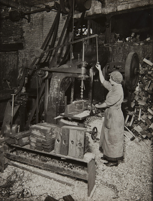 Woman operating boring machine; boring wooden reels for winding barbed wire