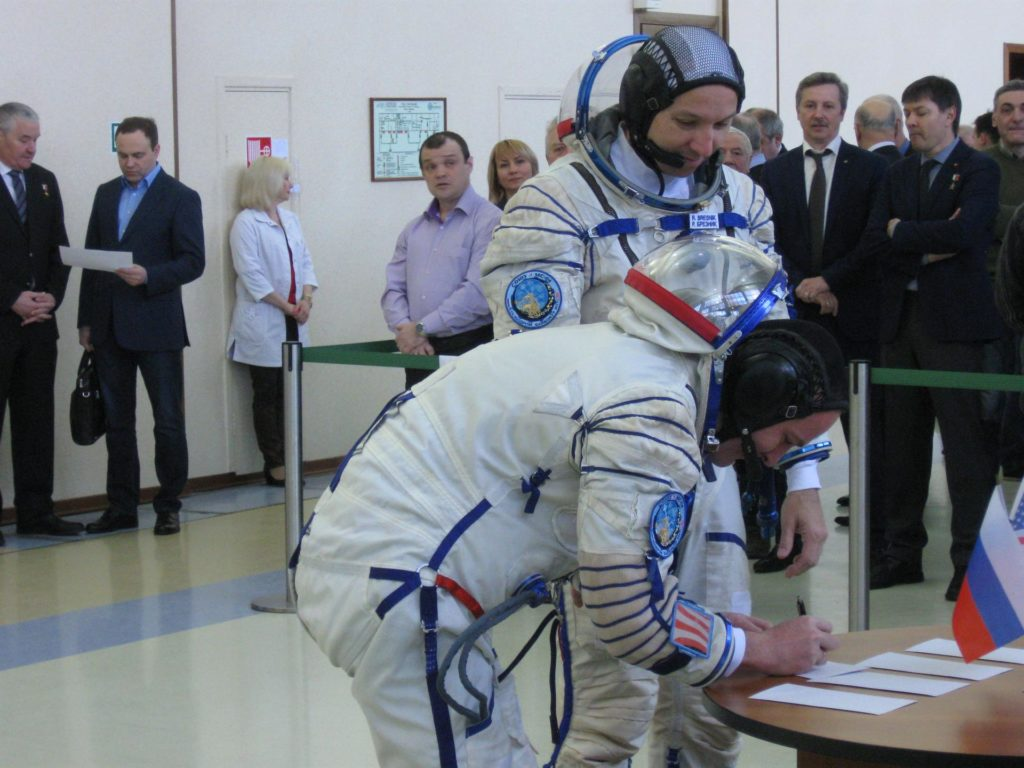jsc2017e038542 (March 30, 2017) --- At the Gagarin Cosmonaut Training Center in Star City, Russia, Expedition 51 backup crewmember Sergey Ryazanskiy of the Russian Federal Space Agency (Roscosmos, left) signs in for the start of final crew qualification exams March 30 as his crewmate, Randy Bresnik of NASA (right) looks on. They are backups to Fyodor Yurchikhin of Roscosmos and Jack Fischer of NASA, who will launch April 20 on the Soyuz MS-04 spacecraft from the Baikonur Cosmodrome in Kazakhstan for a four and a half month mission on the International Space Station. Credit: NASA/Rob Navias jsc2017e038542