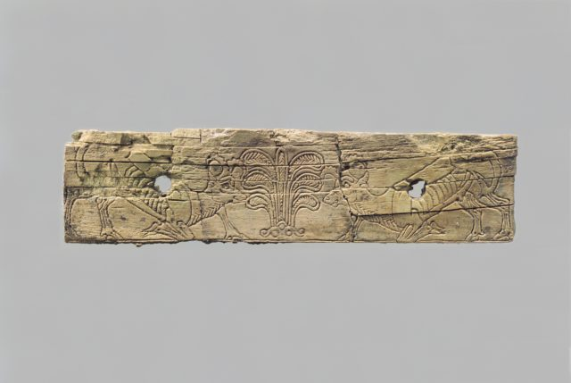 Incised furniture plaque with two ibexes flanking a stylized palmette tree