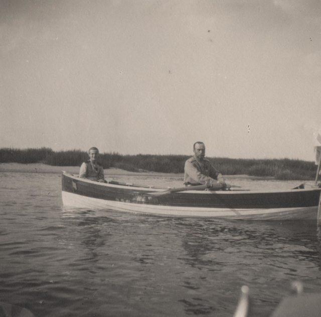 Emperor Nicholas II and Tsarevich Alexei ride a boat.