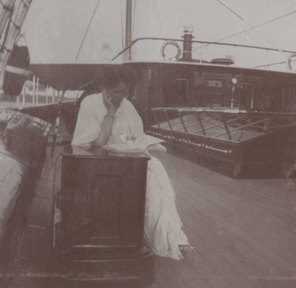 """Empress Alexandra Feodorovna reading a book aboard the Imperial yacht """"Standart""""."""