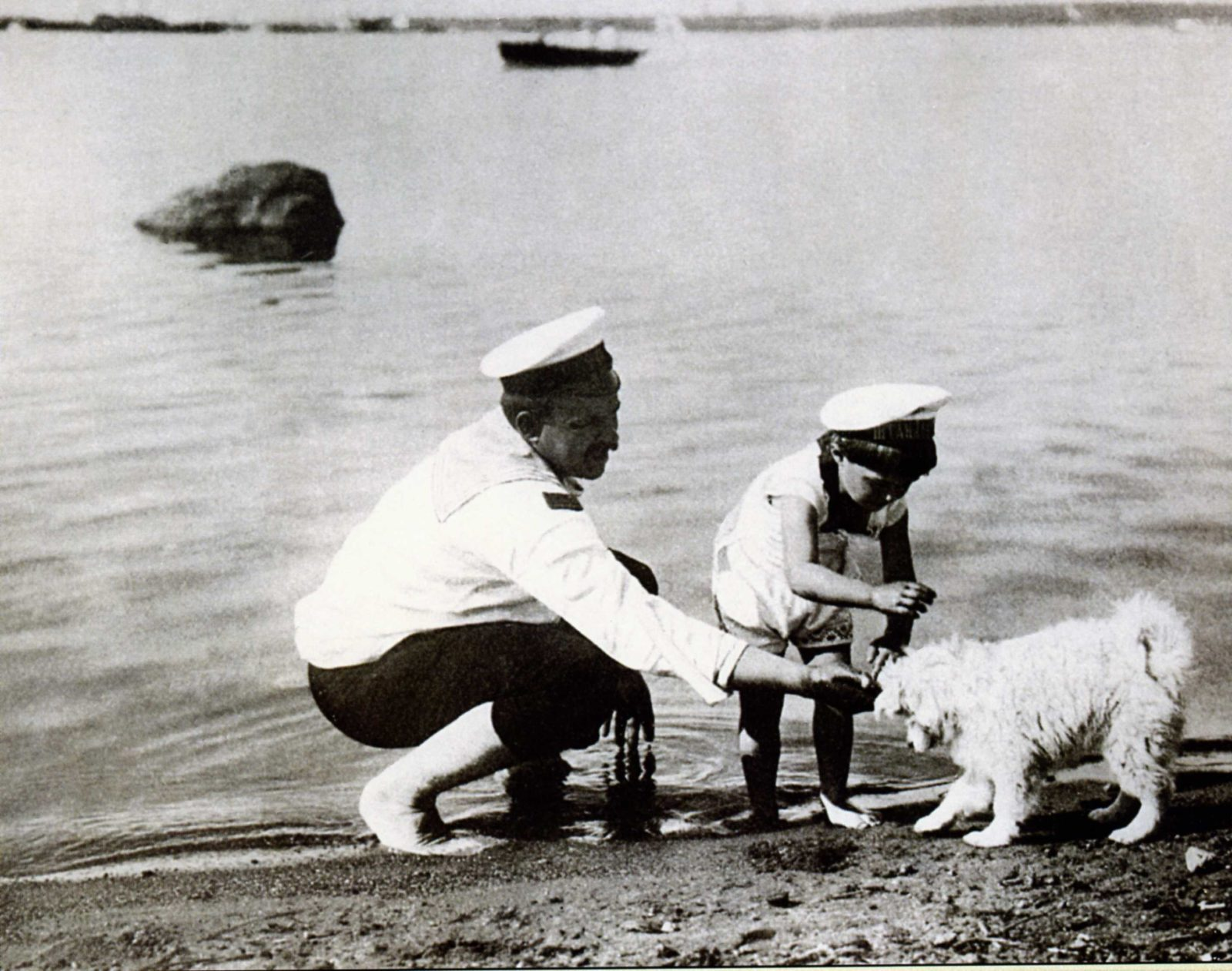 Tsesarevich Alexei Nikolayevich plays with a dog on a walk.