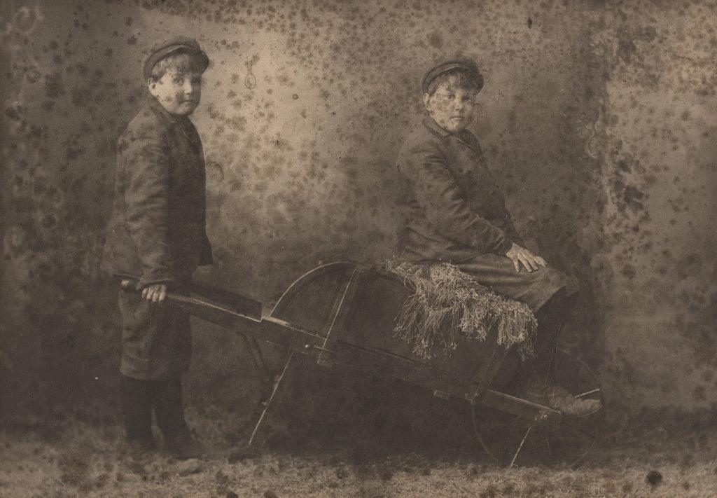 Portrait of two boys with wheelbarrow, date unknown