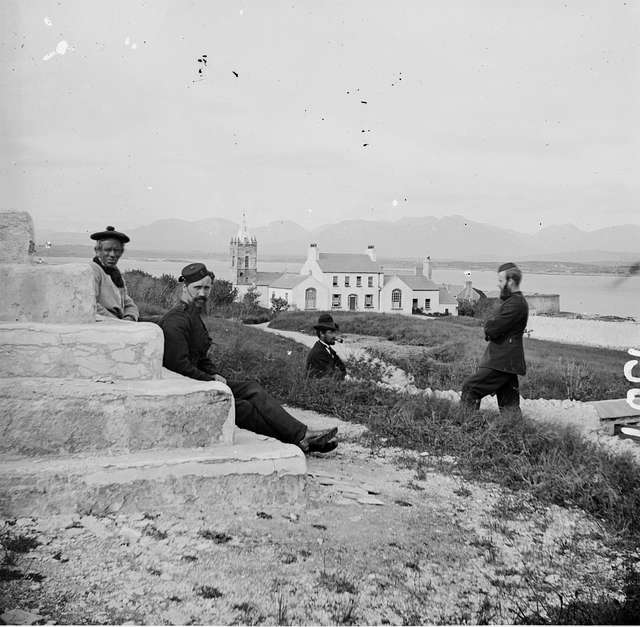 """""""Long shot sea, hills in background, 2 Constables and 2 others at steps or plinth foreground, church with spire…""""  =  ?"""