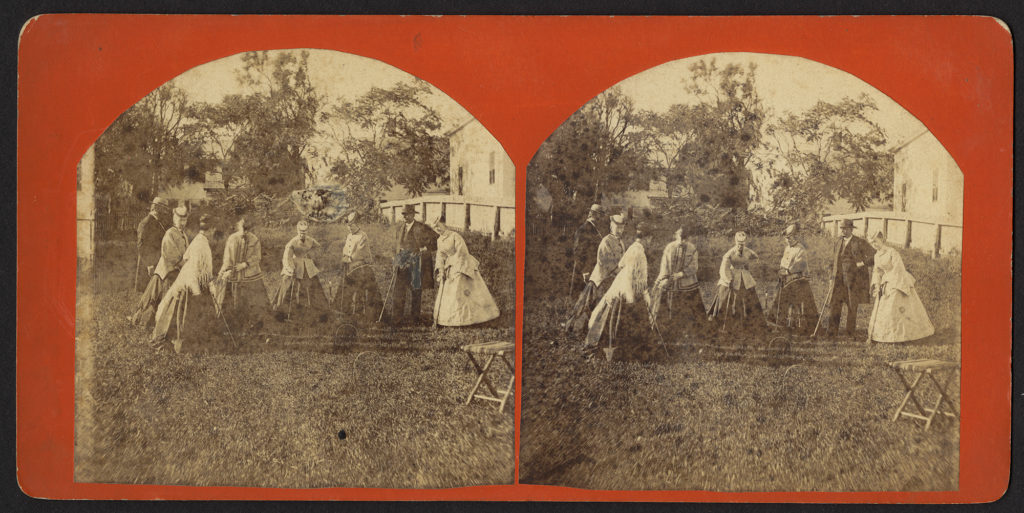 Group of six women and two men playing croquet