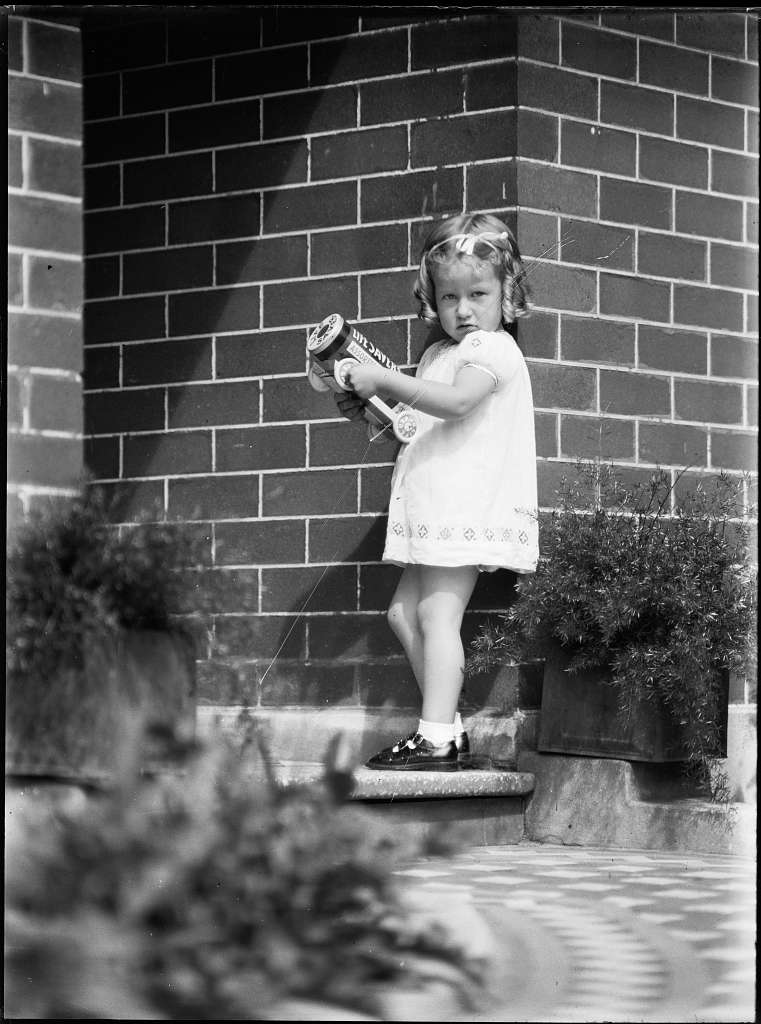 Girl (Cook family) on front doorstep carrying a toy 'Life Savers' truck (3448371239)