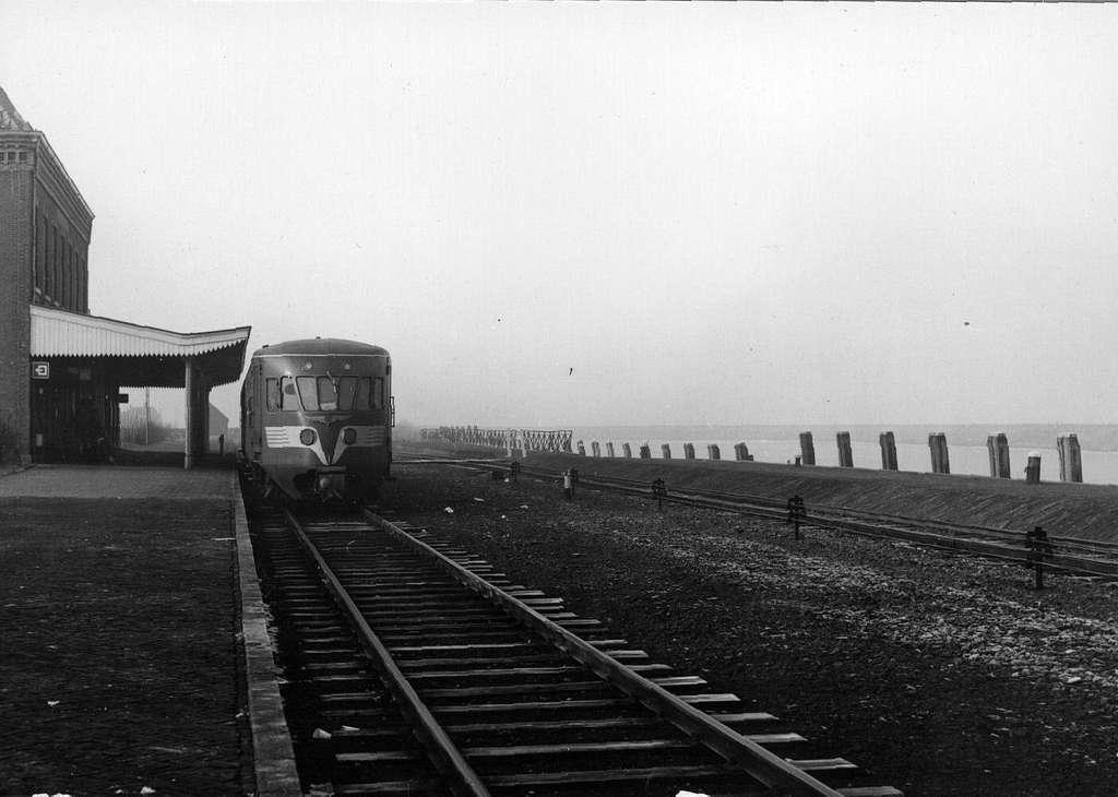 """HUA-153284-Afbeelding van een diesel-electrisch treinstel DE 1 (""""Blauwe Engel"""") van de N.S. langs het perron van het station Stavoren te Stavoren met links het oude stationsgebouw kort voor de afbraak en rechts"""