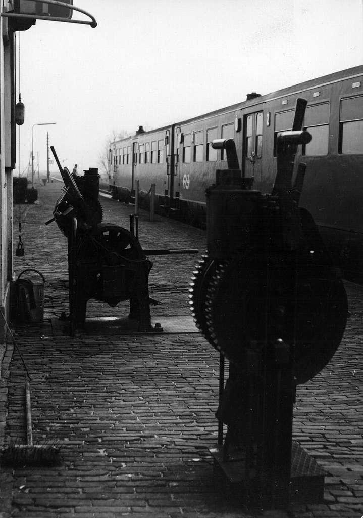 """HUA-153910-Afbeelding van de handelinrichting en het mechaniek voor de overwegbomen op het perron van het N.S.-station Dronrijp te Dronrijp. Langs het perron een diesel-electrisch treinstel DE 2 (""""Blauwe Engel"""","""