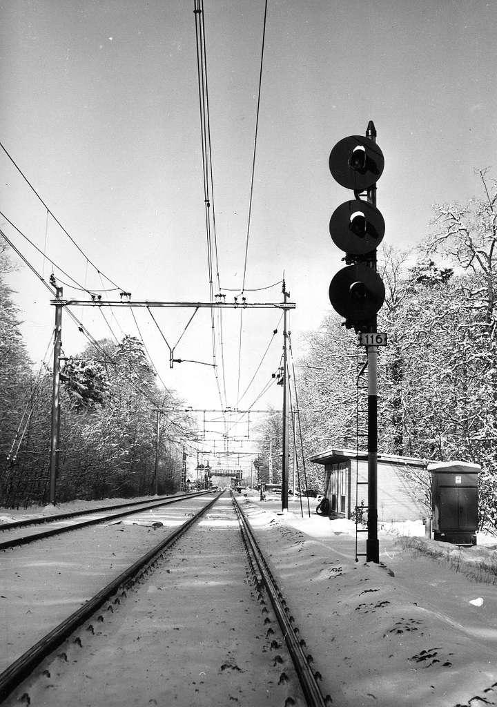 HUA-167153-Gezicht op de spoorlijn bij Driebergen, tijdens winterse omstandigheden, met het driehoogten-lichtsein 116 en daarachter de ploegbergplaats van de Dienst van Weg en Werken