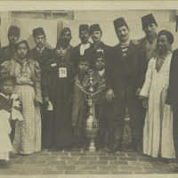 A group of immigrants, most wearing fezzes, surrounding a la...